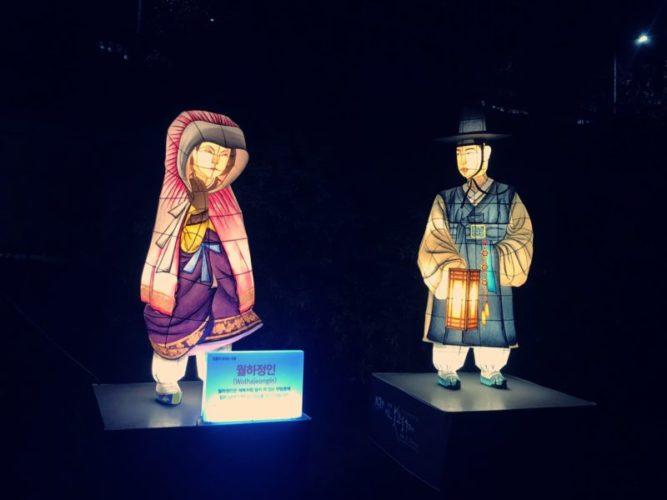 灯りを持った男性と人目を気にする女性のカップル