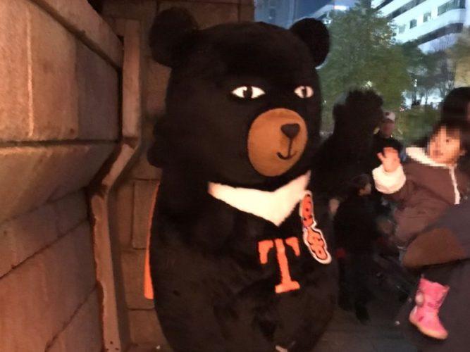 お腹にTと書いてある黒いクマの着ぐるみ