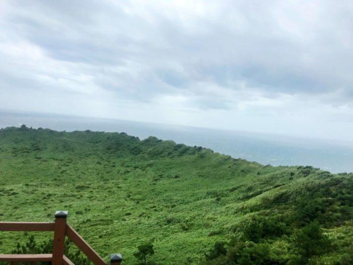 緑で覆われた火口と水平線