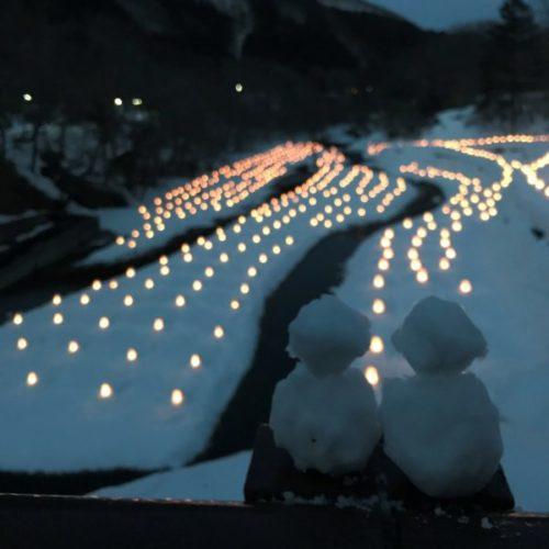 遠くまで延びたミニかまくらの列と、寄り添う2体の雪だるま
