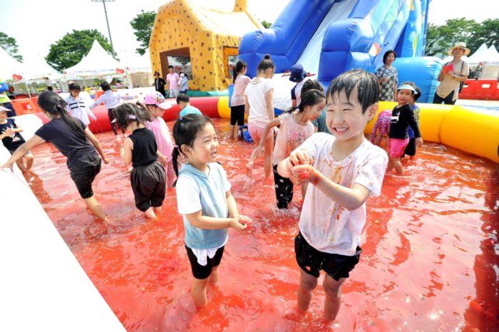 真っ赤に染まったトマトプールで遊ぶ子供たち