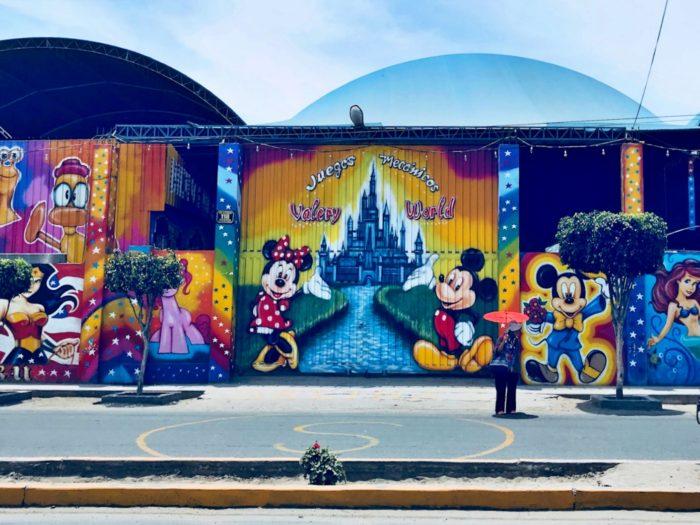 完全なディズニーキャラクターとシンデレラ城が描かれた遊園地の壁