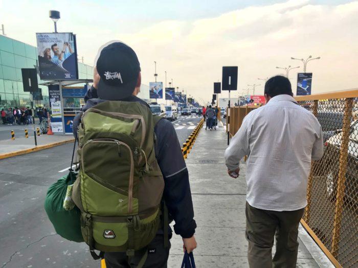 バックパックを背負った彼と運転手さんが歩く空港の外