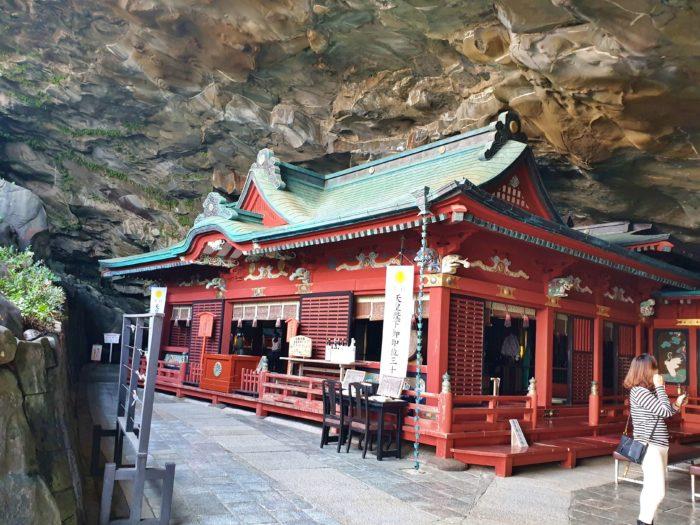薄暗い洞窟の中に存在感のある朱色の本殿